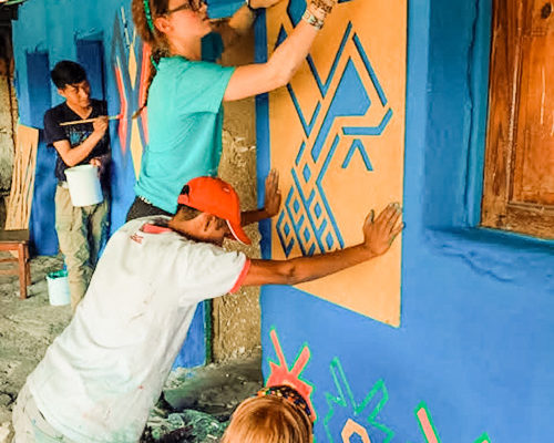 Students and locals working together to repaint a wall while using stencils