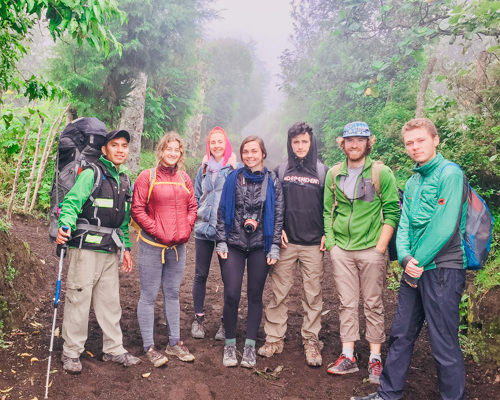 Group of gap year students and their mountain guide pose in a line on a dirt trail while climbing a volcano