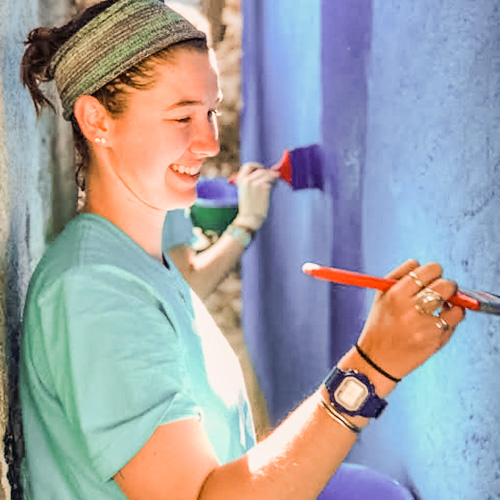 Female student smiling while repainting a bright blue wall