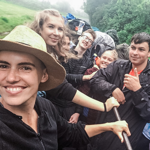 Group of gap year students and staff standing and smiling in the back of a crowded pick up truck