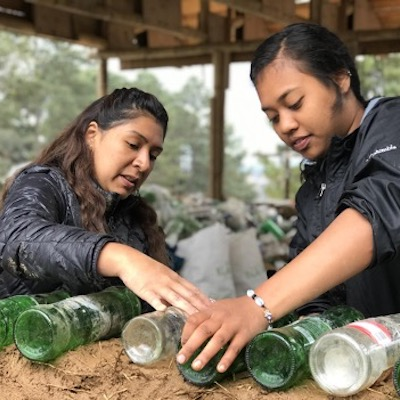 Two gap year students working on a natural building project with recycled glass bottles