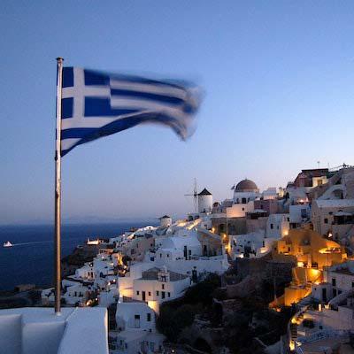 Greek flag flying over a coastal greek community at sunset