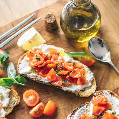 Fresh bread with tomatoes, cheese and olive oil on a wooden table